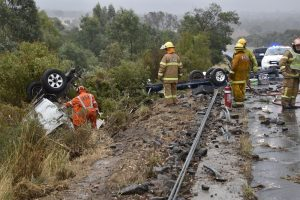 A ute carrying another ute on a trailer crashed into two sets of wire rope barriers on the Calder Freeway at Taradale before flipping and landing in a gully. Photo: IET Systems