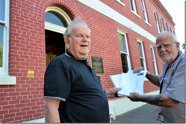 Local Historian Ian Braybrook (right) hands his research on unsung local hero Bill Wadsworth to Castlemaine Pioneers and Old Residents Association president Graeme Barry for safekeeping. Ian and Graeme are pictured here outside Thompson's Foundry where Bill Wadsworth worked last century.