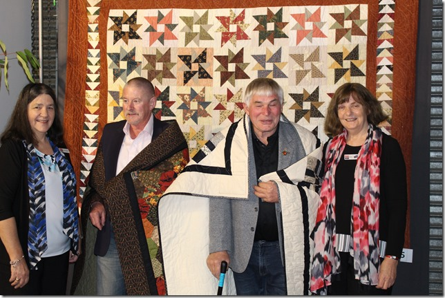 Vietnam veterans Russell McGregor (left) and Robert Renton (right) are presented with their Quilts of Valour by Helen Comport, founder of Quilts of Valour Australia.