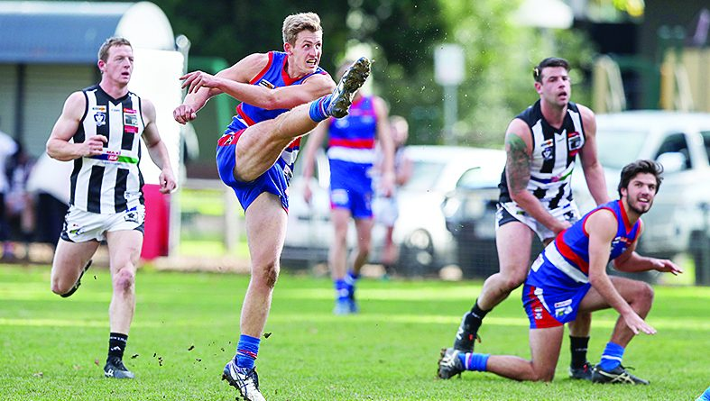 Castlemaine's Kal Huntly shrugs off a tackle from Gisborne's Thomas Wood. Photo: Peter Banko