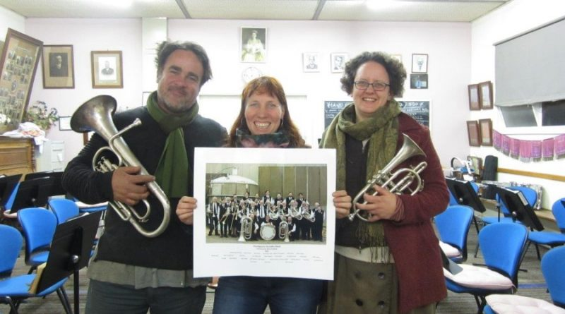 Foundry Band musicians Mark Anstey and Alison Hanley and filmmaker Leonie Van Eyk with a photograph of the local band.