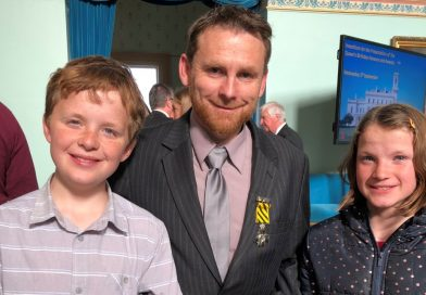 Newstead publican Trevor Mitchell is pictured with his Conspicuous Service Cross and his children Tom and Claire at Government House on September 5.