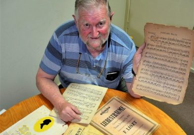 Terry Hodgkins with some of the sheet music left to the Castlemaine Men's Shed by former member Lindesay Hart.