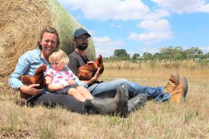 Claire and her partner Paul became the first in Victoria to be granted a low-density mobile poultry planning permit last week. They are pictured with daughter Wren.