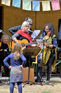Young Minka Neale of Castlemaine looks on as local musicans Kavisha Mazzella and Trudy Edgeley take to the stage during Friday's International Women's Day celebration in the botanical gardens.